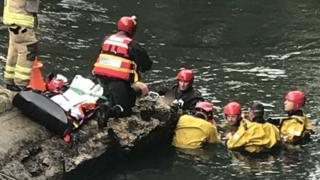 Emergency services trying to rescue the boy from the river