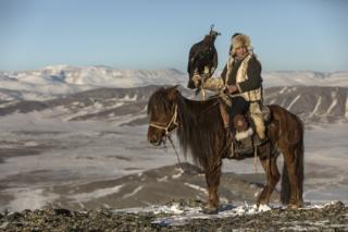 девушка верхом на лошади с беркутом