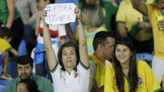 """A fan in the stands holds a sign that reads in Portuguese """"Temer Out"""" prior a group E match of the women's Olympic football tournament between Brazil and Sweden at the Rio Olympic Stadium in Rio De Janeiro, Brazil, Saturday, Aug. 6, 2016."""