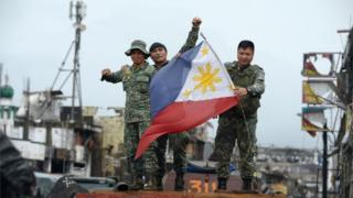 "Philippine soldiers aboard their armoured personnel carrier celebrate after President Rodrigo Duterte declared Marawi City ""liberated"", inside the battle area of Bangolo in Marawi on October 17, 2017."