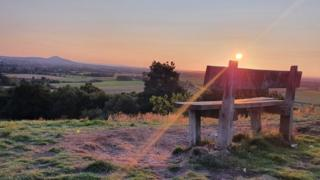 Sunset over a bench overlooking fields