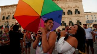 People celebrate after the Maltese parliament voted to legalise same-sex marriage on the Roman Catholic Mediterranean island, in Valletta, Malta