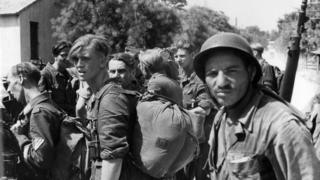 A French Algerian soldier guards captured German troops at Ste Marthe, southern France, August 1944