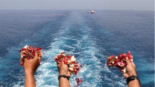 Families and colleagues of passengers and crew of Lion Air flight JT610 throw flowers and petals from the deck of Indonesia Navy ship KRI Banjarmasin as they visit the site of the crash to pay their tribute, at the north coast of Karawang, Indonesia, 6 November 2018.