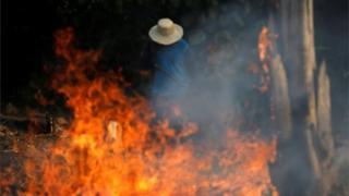 Homem diante de fogo na Amazônia