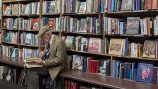 man reading in bookshop