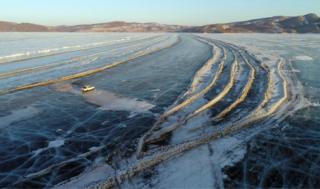 A car drives along a road connecting the banks of the ice-covered Yenisei River