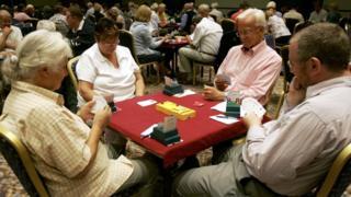 Two couples playing bridge
