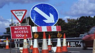 Car drives past a works access sign