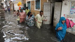 Люди идут по затопленной улице