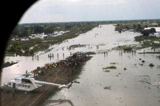 A WFP (World Food Program) helicopter is seen on the flooded airstrip, after heavy rains and floods forced hundreds of thousands of people to leave their homes, in the town of Pibor, Boma state