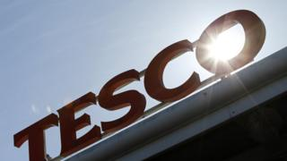 Tesco sign with sun behind it