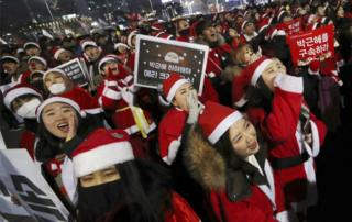 People wearing Santa Claus costumes shout during a rally calling for South Korean President Park Geun-hye to step down in Seoul, South Korea, on 24 December, 2016.