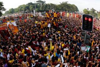 Huge crowds of Filipino devotees jostle to reach the statue of the Black Nazarene during the procession in Manila, Philippines, 9 January 2017.