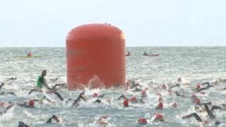 Swimmers swim in Carmarthen Bay