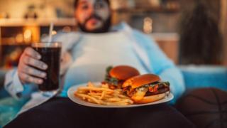 Hombre sentado en un sofá degustando una comida rica en grasas.
