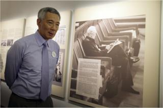 Singapore's Prime Minister Lee Hsien Loong walks past an old photograph of his father, the late Lee Kuan Yew during a remembrance ceremony held at the old Parliament House to mark the first death anniversary of Singapore's founding Prime Minister Lee Kuan Yew on Wednesday, 23 March 2016, in Singapore