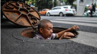 A man worksing in a manhole in Chengdu, China