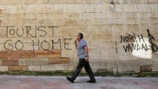 "A man walks past a ""Tourists Go Home"" graffitti on a wall close to the City Hall in Oviedo, northern Spain,"