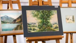 Watercolour paintings are displayed on an easel