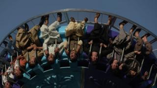 Afghan visitors ride a fairground ride at the Park Shahar or City Park, in Kabul