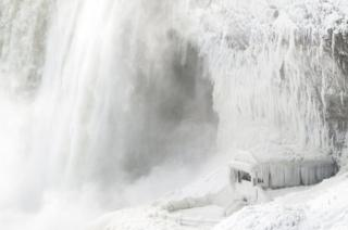 Ice coats the rocks and observation deck at the base of the Horseshoe falls.