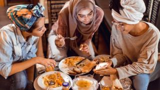 Group of women eating food including chips