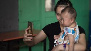 A woman takes a selfie with a baby on a street in Beijing