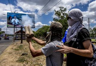 Masked students fire their home-made mortars at a big poster of President Daniel Ortega and his wife, Vice-President Rosario Murillo