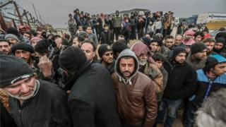Syrians gather at the Bab al-Salam border gate with Turkey, in Syria, Saturday, Feb. 6