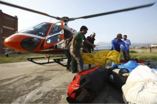 Officials carry the bodies of Indian climbers recovered from Mount Everest and airlifted to Teaching Hospital in Kathmandu on May 28, 2017.