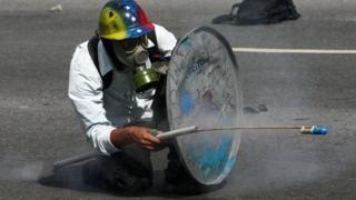 opositor venezolano con un escudo de lata