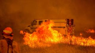 A fire vehicle is surrounded by flames as the Pawnee fire jumps across highway 20 near Clearlake Oaks, California on 1 July 2018