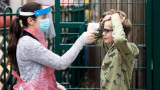 A member of staff takes a child's temperature at a school in London - 4 June 2020