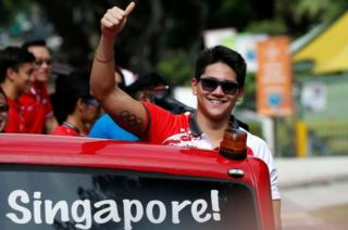 Singapore's Olympic gold medallist swimmer Joseph Schooling gestures during a victory parade on an open top bus in Singapore August 18, 2016.