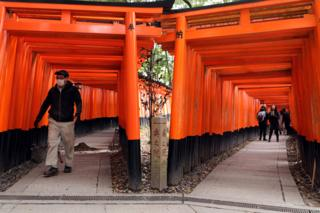 A construction man wears a face mask while walking through the empty Torii gates of Fushimi Inari Taisha Shrine that are usually overrun by tourists on March 06, 2020 in Kyoto, Japan