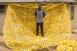 Serge Clottey standing on one of his tapestries in La - Accra, Ghana