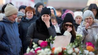 People mourn the victims of a shopping mall fire at a makeshift memorial in the Siberian city of Kemerovo, 26 March