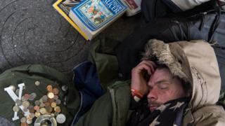 مرد بی خانمان که کنار خیابان خوابیده است