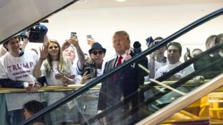 Donald Trump makes his entrance via a golden escalator