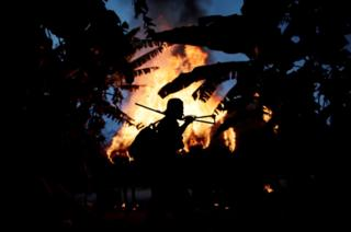 A man from the Guajajara community stands by a fire at a loggers camp