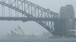 The Sydney Opera House and Sydney Harbour Bridge seen through a cloak of heavy rain