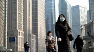 People wearing protective face masks walk on an overpass in Shanghai on February 24, 2020