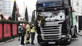 This file photo taken on December 20, 2016 shows firemen inspecting the truck that crashed the evening before into a Christmas market in Berlin.