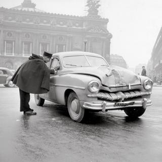 A policeman talks to the driver of a car after an accident