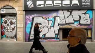 Members of the public walk past a closed shop as new measures against the coronavirus expansion are implemented on March 14, 2020 in Barcelona, Spain.