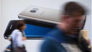 Transeúntes frente a un afiche del Galaxy Note 7.