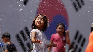 A South Korean girl is splashed with water as she stands in front of her country's flag.