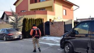 A Slovak policeman walks outside a house linked to Italian businessman Antonin Vadala during a police search