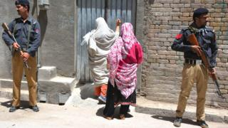 Pakistani police guard a health worker home-visit during a polio vaccination campaign in Quetta, 26 April 2016.
